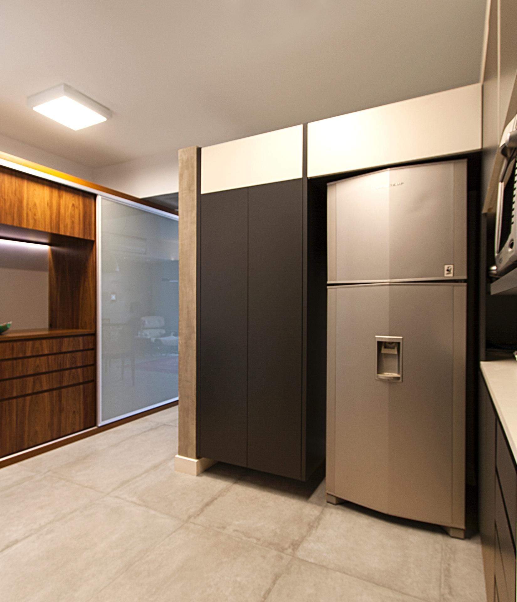 Os equipamentos de cozinha - armários, geladeira e fornos - do apê Raul Poméia, reformado pelo Hiperstudio, ficam escondidos atrás da parede que a separa da sala de jantar. O revestimento dos armários é em laminado melamínico nos padrões branco e petróleo (Eco Wood). Apesar de integrada com a sala, não é possível ver a cozinha à partir da mesa para refeições, pois a ligação se dá por um zigue-zague entre paredes recortadas e rentes