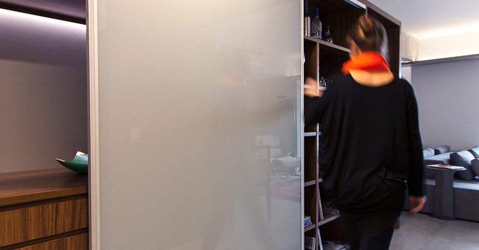 A porta de correr em vidro leitoso para a marcenaria (Eco Wood) serve para mostrar e/ou esconder as múltiplas funções que acompanham o móvel-coringa ora atendendo cozinha, com aparador e faqueiro, ora servindo a sala de jantar, com adega e nichos-prateleiras em jogo não linear