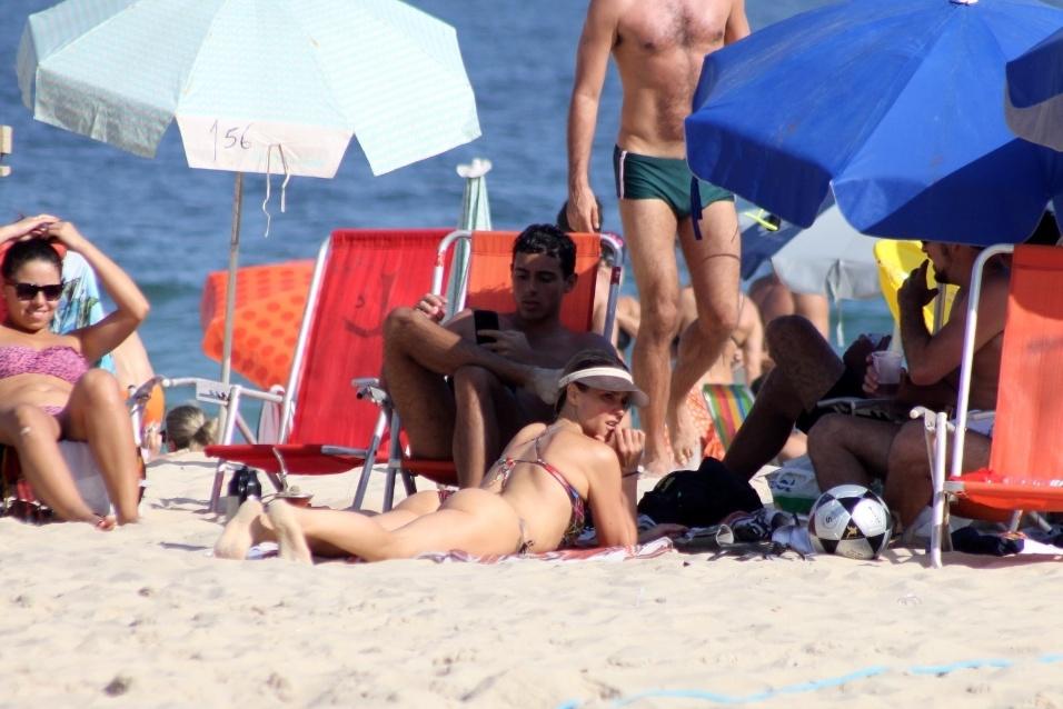 2.nov.2014 - Apresentadora Fernanda Lima se bronzeia na praia do Leblon, no Rio de Janeiro, e protege o rosto com um boné