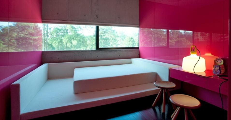 No segundo andar há três dormitórios com acabamento alto brilho para marcenaria na cor magenta. Os painéis chegaram prontos à obra. A cama