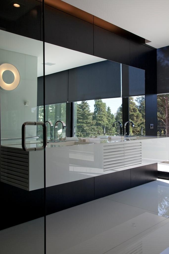 O banheiro do proprietário, no nível da área social (terceiro andar), tem duas pias e bancada feitas com superfície cristalizada de vidro (Marmoglass) branca, moldada. As gavetas com portas venezianas brancas contrastam com o resto da marcenaria, em madeira ebanizada. O piso também é revestido com Marmoglass. O projeto de interiores é de Marcos Bertoldi, para a casa Vertical, em Curitiba (PR)