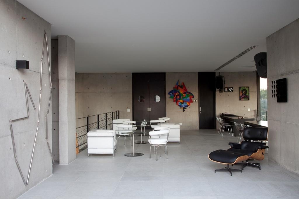 No mezanino, a escultura de parede (à esq.) é de Eliane Prolic, trata-se de um móbile que pode ser montado de jeitos variados. O mobiliário é composto por poltrona Charles & Ray Eames e sofás e poltronas Le Corbusier. Ao fundo, a porta maior é para a cozinha-garçom e a churrasqueira; à direita fica o acesso à sauna e ao vestiário. O projeto de arquitetura e de interiores da residência em Curitiba (PR) é do escritório Marcos Bertoldi Arquitetos