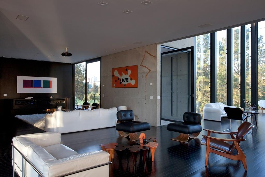 Ao fundo, o home theater da casa Vertical, que separa a suíte máster da sala principal de recepções, no terceiro andar. No projeto original de Marcos Bertoldi, esta sala era limitada por portas de correr, mas o espírito festeiro do morador não aprovou a ideia. Assim, o espaço foi integrado à área mais ampla de convívio social. Na parede, escultura de Eduardo Suéde. No mobiliário destaque para a dupla de poltronas projetadas por Oscar Niemeyer e para a mesa de centro desenhada pelo Estúdio Bola