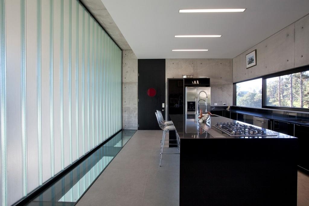 A cozinha principal, no segundo andar (terceiro pavimento), é dedicada à família. O revestimento em alto brilho na cor magenta (à dir.) denuncia sua localização na casa. À esquerda, a faixa com piso de vidro intensifica a entrada de luz natural, de baixo para cima. A vista, através da janela-fita com folhas móveis de correr (a mesma que vem dos dormitórios das crianças), é para o campo de golfe. A residência projetada por Marcos Bertoldi fica em Curitiba (PR)