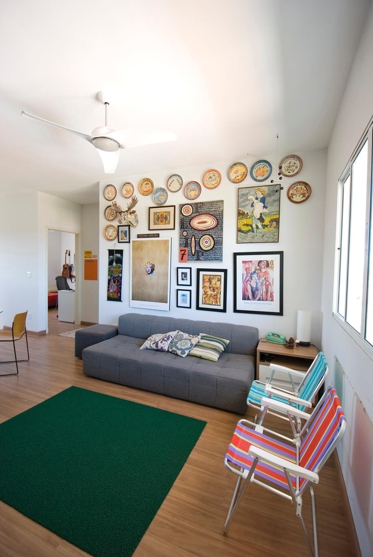 Com um orçamento limitado, o arquiteto Leandro Matsuda buscou soluções baratas para o apartamento alugado em Mogi Mirim (SP). Na sala de estar, no lugar de poltronas tradicionais, duas cadeiras de praia (Leroy Merlin) foram combinadas a um tapete de borracha (Monlline), com efeito de grama sintética. Atrás do sofá (Tok&Stok) de cor cinza, quadros, pratos decorativos e outros objetos, na maioria deles, trazidos de viagens pelo cliente, preenchem a parede numa composição despojada