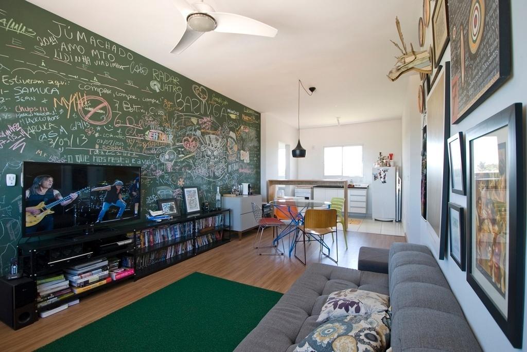 Elemento central e interativo, que conecta as salas de estar e jantar, a parede pintada com tinta lousa traz registros divertidos e coloridos dos convidados do morador do apartamento, em Mogi Mirim (SP). Soluções em conta, como o rack da TV, montado com prateleiras metálicas (Método Móveis) usadas em escritórios, personalizam o imóvel alugado e dão um ar de descontração. Na área de jantar, uma mesa com tampo de vidro é combinada a cadeiras de design moderno e variado