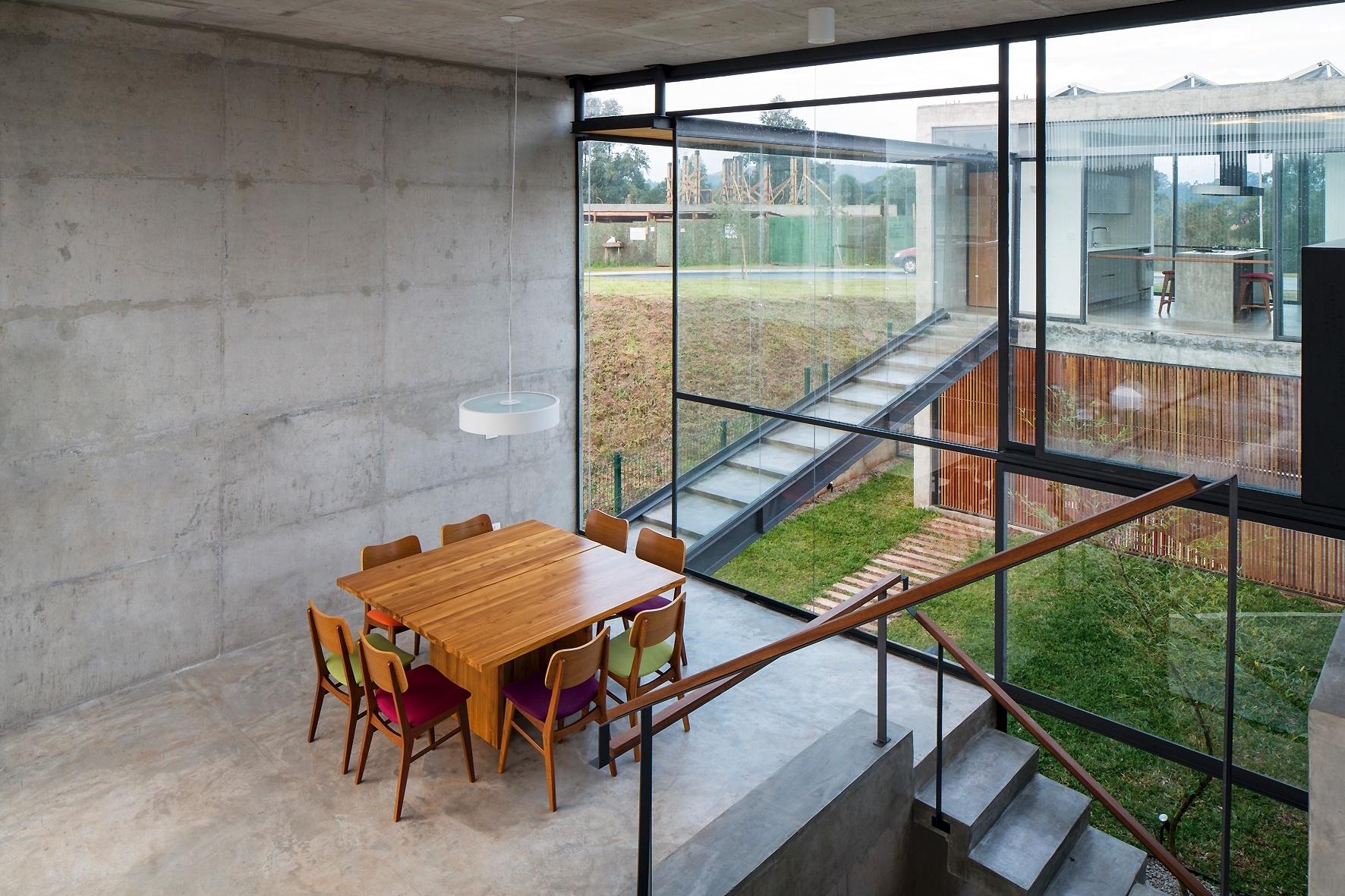 A sala de jantar da Casa Itahyê, projetada pelo escritório Apiacás Arquitetos, possui ligação com vários ambientes, como com a cozinha através da rampa-escada; a sala de estar acima e o pátio abaixo via escadas. A mesa e as cadeiras são assinadas por Fernando Jaeger