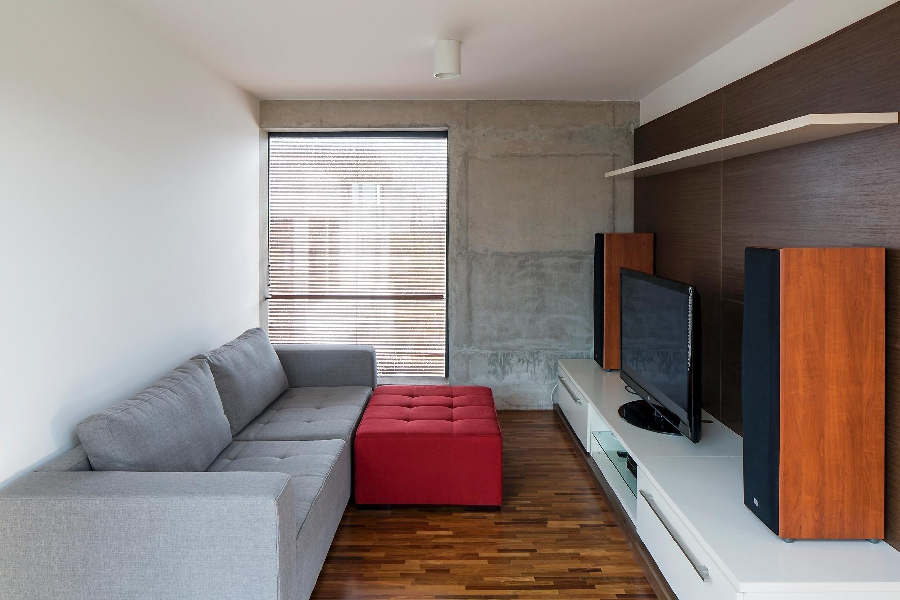 No nível inferior e contígua à suíte, a saleta íntima tem piso de madeira e funciona como home theater. O sofá e o pufe são assinados pelo designer Fernando Jaeger,enquanto a bancada para TV é da Ornare e a luminária, da Reka. A Casa Ithayê foi projetada pelo escritório Apiacás Arquitetos