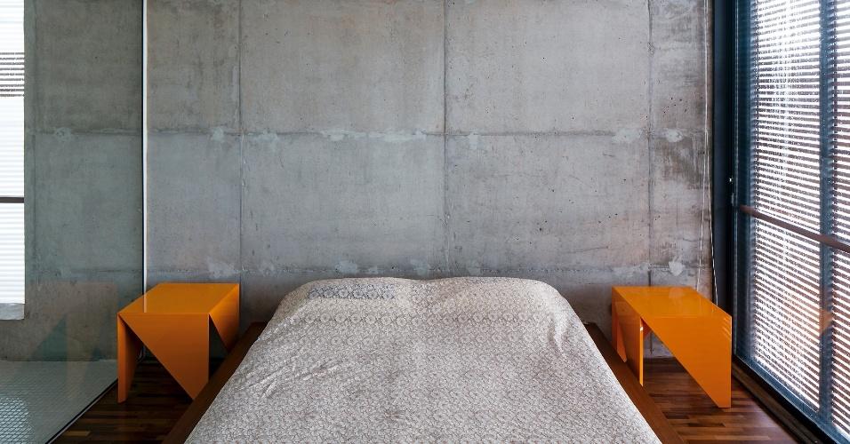 A decoração minimalista da suíte principal inclui apenas a cama da Marcenaria São Paulo e os bancos do Estúdio Bola fazendo as vezes de mesinhas de cabeceira. À esquerda, destaque para a integração do espaço de descanso com o banheiro, separado dele apenas por painel de vidro. A Casa Ithayê foi projetada pelo escritório Apiacás Arquitetos