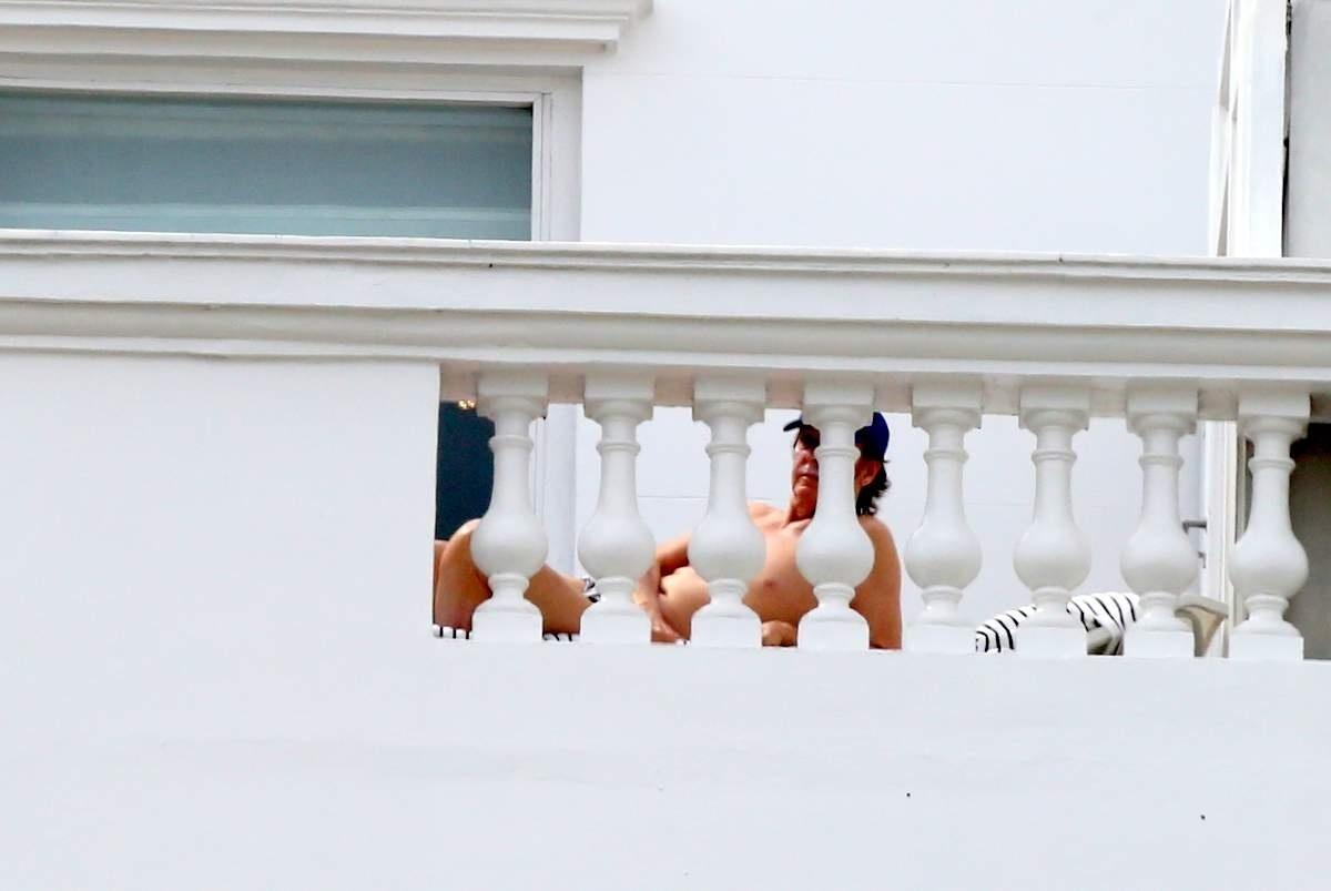 12.nov.2014 - Usando um boné, Paul McCartney toma banho de sol na varanda do hotel Copacabana Palace, no Rio