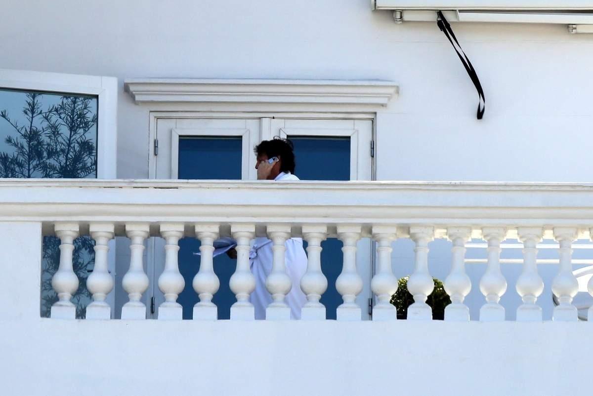 12.nov.2014 - Com show marcado para a noite desta quarta no Rio, Paul McCartney fala ao telefone na varanda do hotel Copacabana Palace