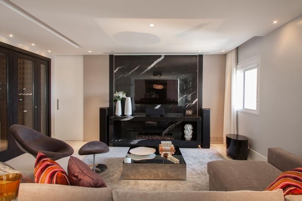Neste home theater, a designer Silvia Romanholi adotou variantes do cinza como base: as paredes mais clarinhas sofrem o efeito
