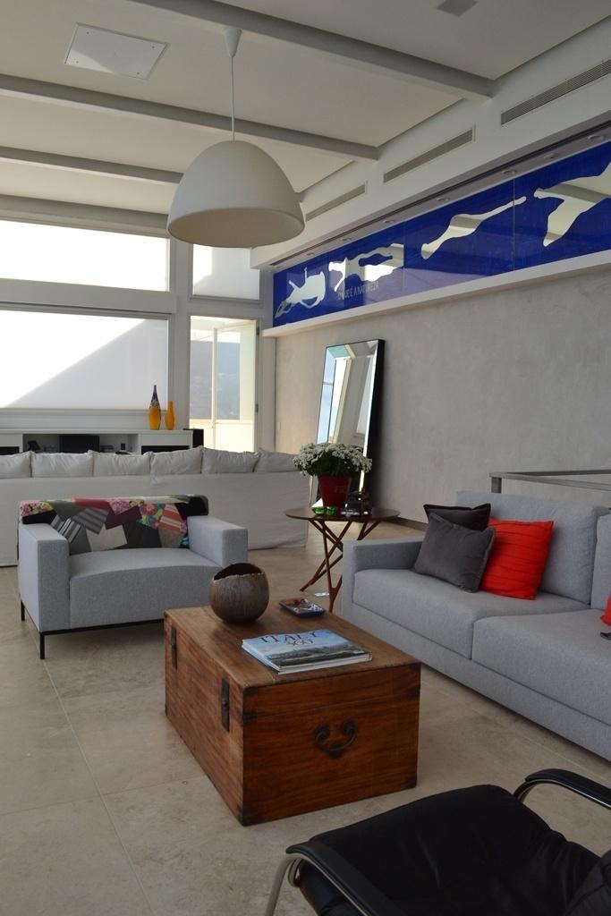O arquiteto André Piva recorreu ao cinza no living claro, para que a obra assinada por Carlito Carvalhosa - onde o azul predomina - e a natureza revelada pela ampla janela ficassem em destaque. Também sobressaíram à base cinzenta a madeira e as cores das almofadas