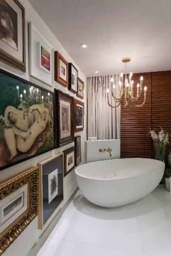 Na sala de banho da Suíte do Casal 2, de Ana Paula Guimarães e Thiago Manarelli, sobre a banheira pende uma releitura do lustre bengala dos anos 1950 (La Lampe/ Dominici). Destaque também para a parede