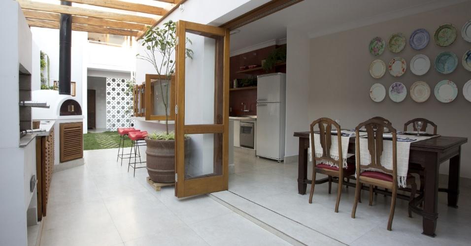 A cozinha (à dir.) é integrada ao espaço gourmet por portas articuladas (camarão): o novo ambiente ocupa o espaço da antiga lavanderia (corredor lateral) e se tornou uma área de lazer e de recepção da casa, com churrasqueira e forno de pizza, além de um pergolado em madeira de demolição. O projeto da SET Arquitetura orientou o