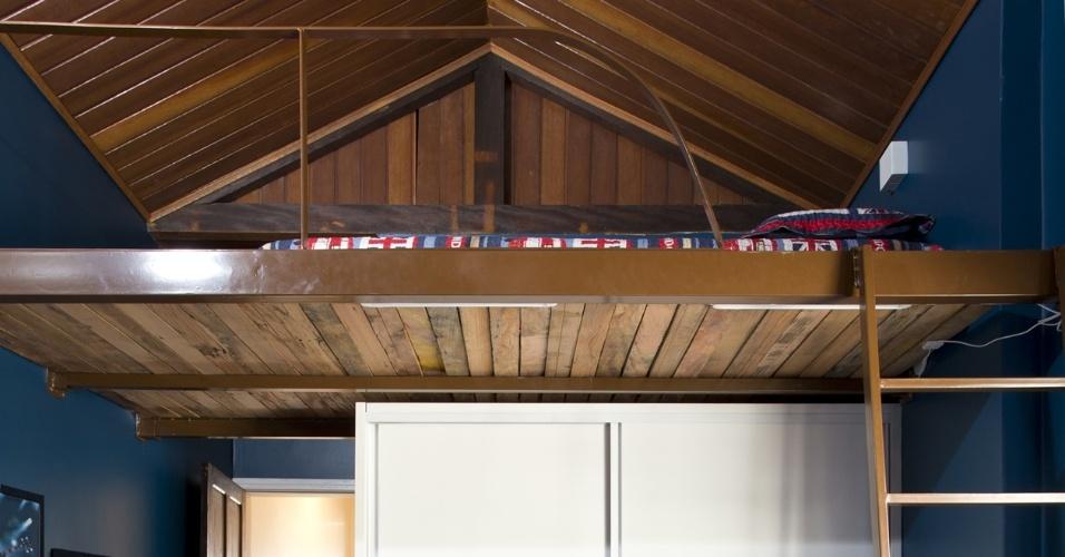 Localizada na fachada posterior da casa, uma antiga varanda foi incorporada à área íntima do dormitório. A cama suspensa por tablado desmontável (2,65 m x 1,4 m) é sustentada por espessos perfis metálicos chumbados nas paredes laterais. O leito está a 2,2 m do piso e ainda sobram 1,60 m dela até o ponto mais alto do forro - este acabado em cedro rosa. Para otimizar ainda mais o espaço, a marcenaria para guarda-roupa foi encaixada sob o tablado pelos profissionais do escritório SET Arquitetura