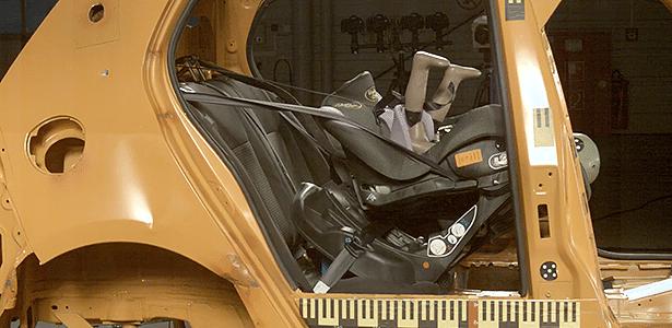 Presilha da cadeirinha Baby Style 333 quebra durante teste, e boneco quase dá cambalhota; numa situação real, bebê bateria a cabeça no banco dianteiro