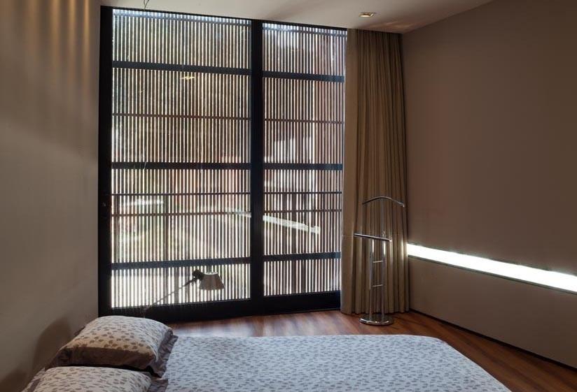 O dormitório do casal apresenta uma atmosfera sóbria e intimista graças à pintura escurecida das paredes e ao piso em cumaru. Destaque para o rasgo horizontal (à dir.) que permite a entrada de luz natural. A NSN House foi projetada pelo escritório Biselli Katchborian Arquitetos e fica localizada em Curitiba (PR)