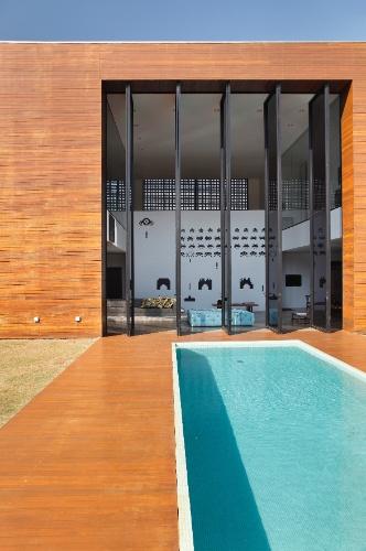 A entrada da LA House, projetada pelo Studio Guilherme Torres é marcada pela imponência das portas pivotantes com sete metros de altura, onde se situa o estar de pé-direito duplo. A parte externa é ocupada pela piscina cercada por deck de madeira