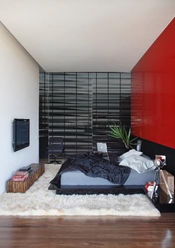 O painel vermelho na parede concede boas energias ao dormitório do casal e contrasta com a cama baixa e a cabeceira em preto. A LA House é um projeto do Studio Guilherme Torres