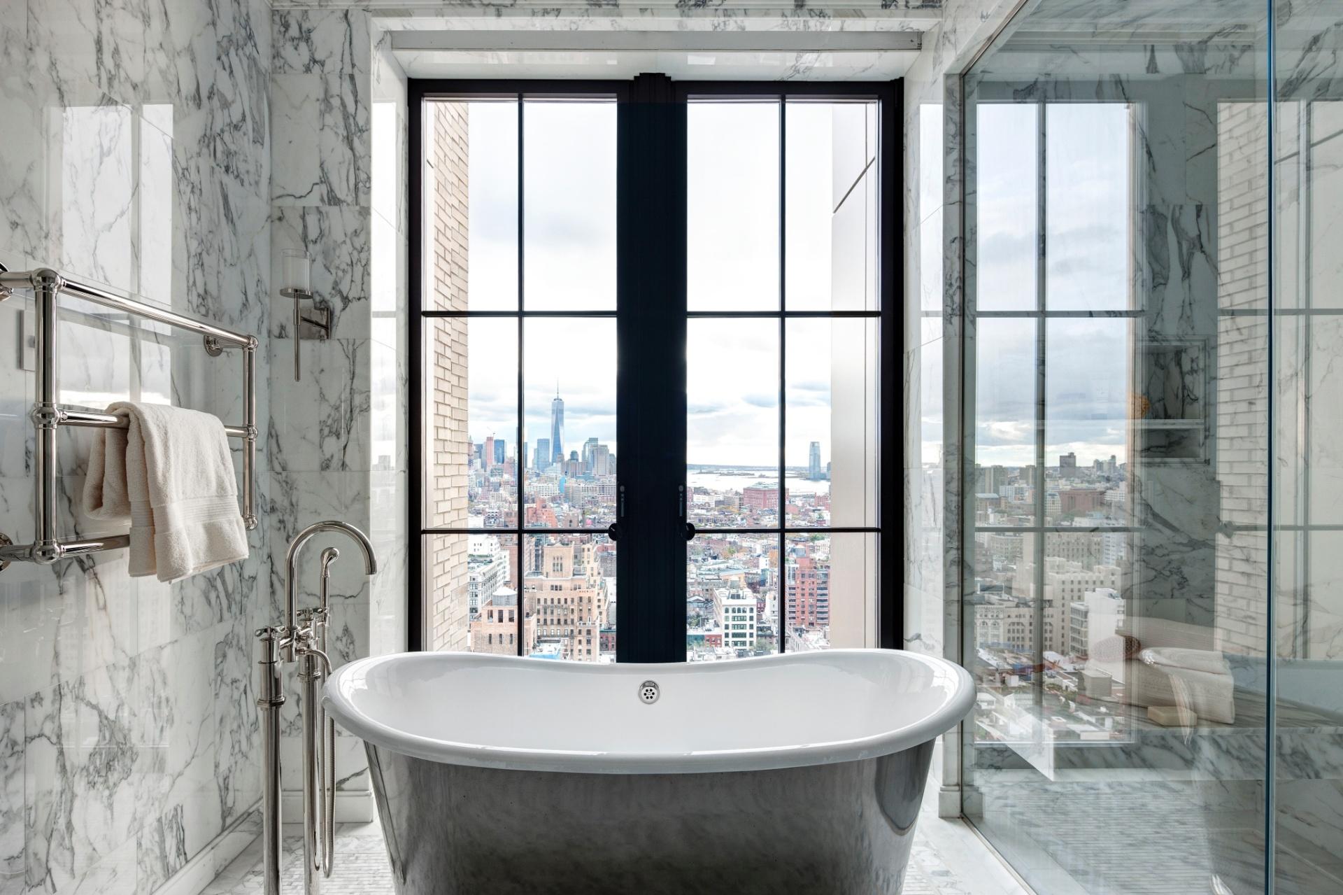 No edifício Walker Tower, localizado na rua 18th West, o banheiro da cobertura é revestido por mármore e tem portas-balcão com envidraçamento generoso. Em frente a uma delas, está posicionada uma elegante banheira com acabamento externo metálico. Ao fundo, na paisagem, é possível avistar o rio Hudson e, à esquerda, uma das torres do novo World Trace Center - Imagem do NYT, usar apenas no respectivo material