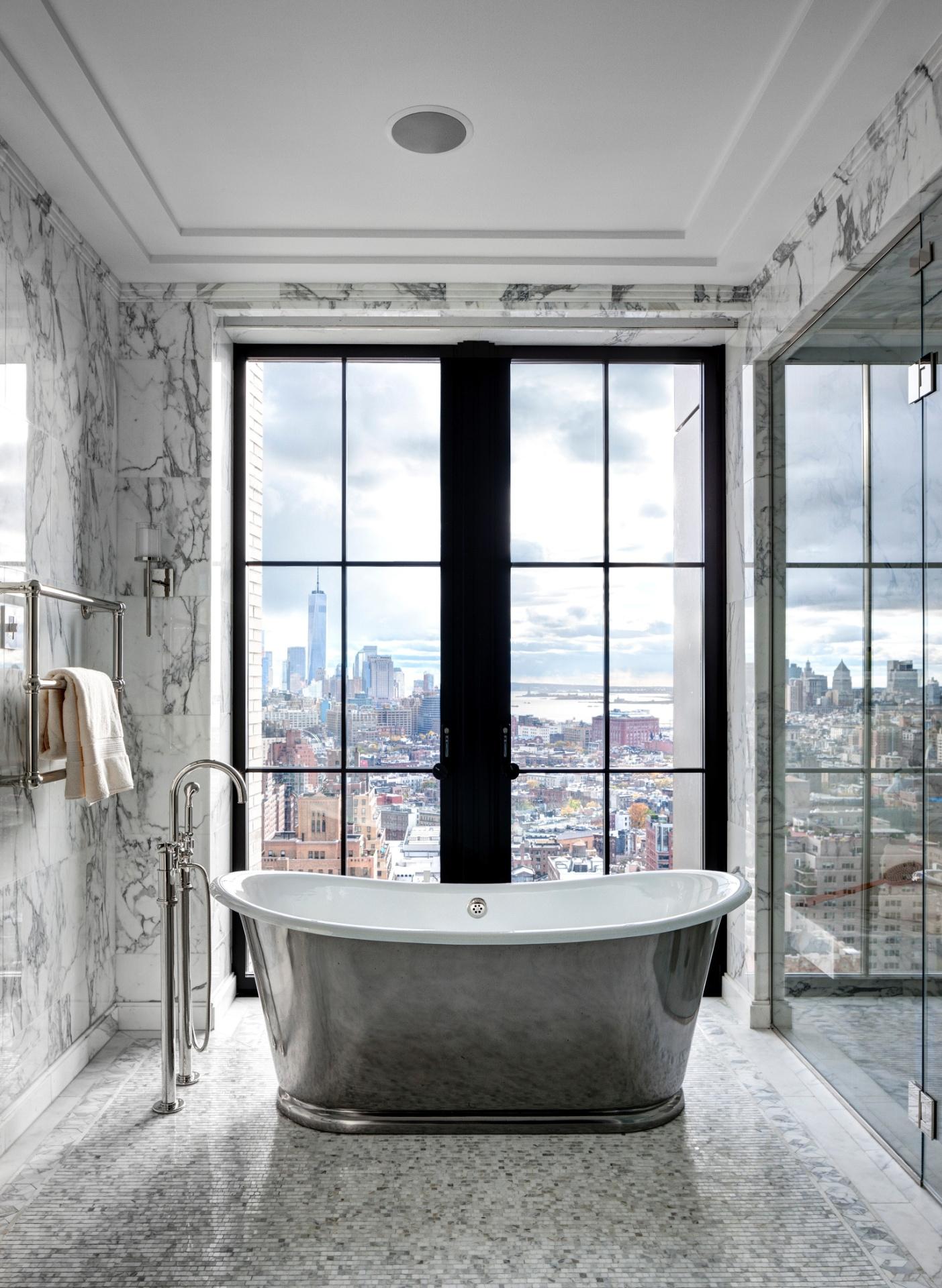 No edifício Walker Tower, localizado na rua 18th West, o banheiro da cobertura é revestido por mármore e tem portas-balcão com envidraçamento generoso. Em frente a uma delas, está posicionada uma elegante banheira com acabamento externo metálico - Imagem do NYT, usar apenas no respectivo material