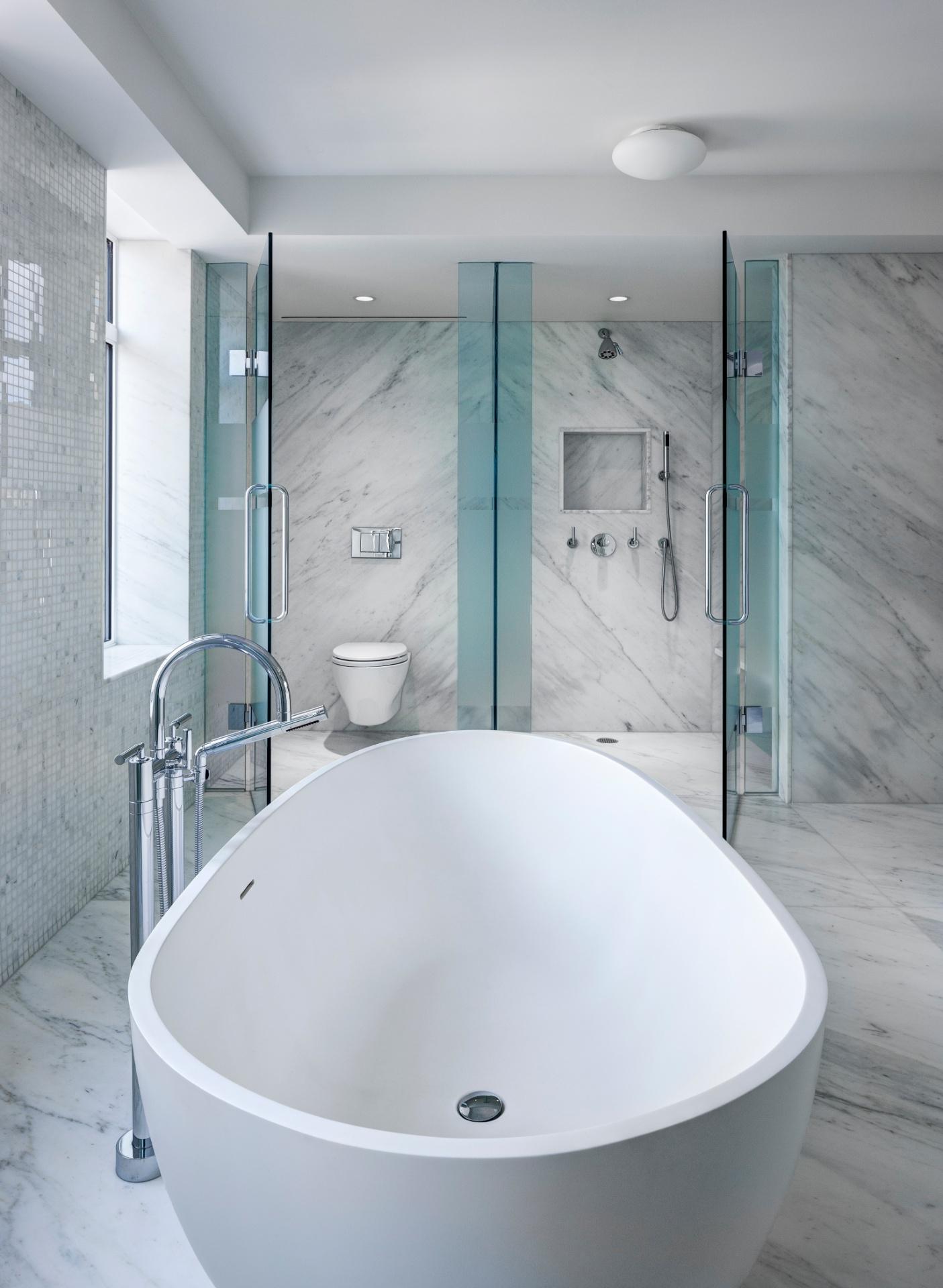 ... a banheira é posicionada de modo a ter todas a sua área limite livre para acesso  do usuário. No espaço (ao fundo), a cabine para banho e o reservado são limitados por boxes de vidro - Imagem do NYT, usar apenas no respectivo material
