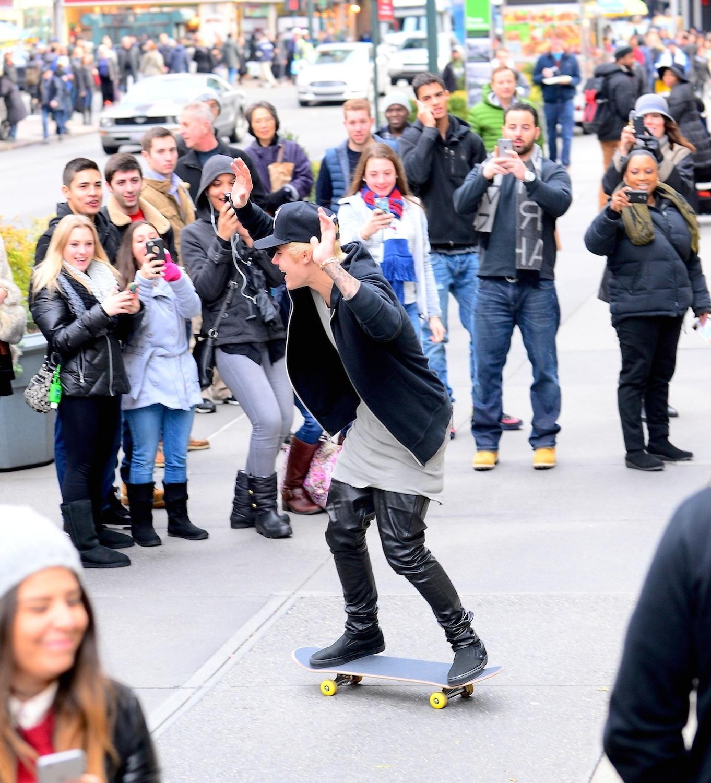 Justin Bieber surpreende os fãs ao andar de skate na Time Square, em Nova York nos Estados Unidos