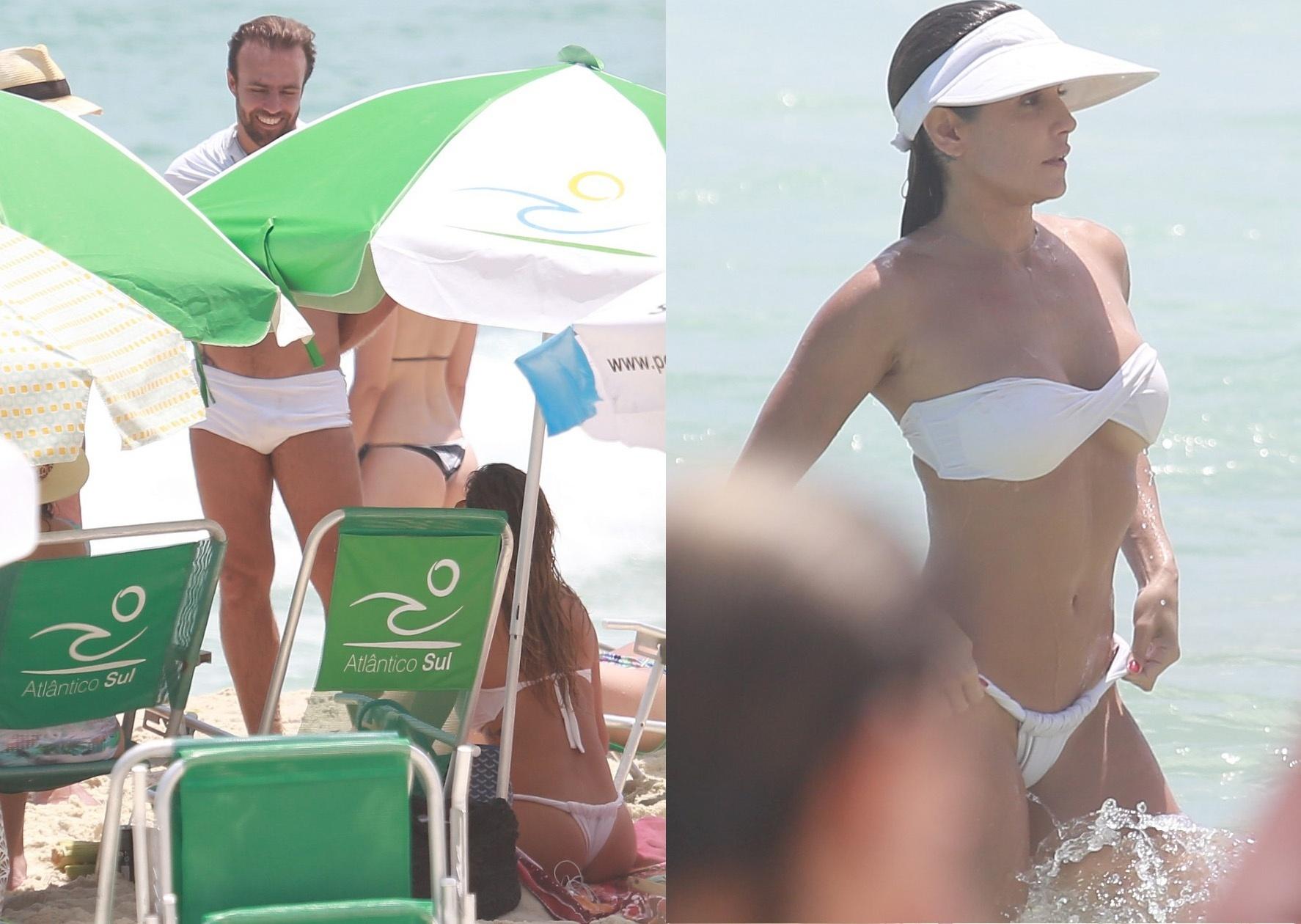 31.dez.2014- De biquíni branco, Deborah Secco se despede de 2014 na praia da Barra da Tijuca, no Rio, e bate papo com o ex-namorado Roger Flores