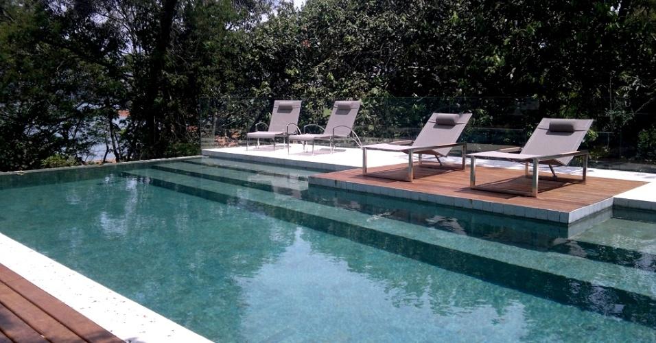 A estrutura desta piscina (12,5 m x 4,5 m), projetada pela arquiteta Kika Prata, é de concreto armado, lançado em um terreno com desnível de cinco metros para onde se volta a borda infinita, criando a queda d'água com quatro metros no jardim. O piso é de fulget e o revestimento é de pedra Greenstone (15 cm²), de Bali, e quando ne