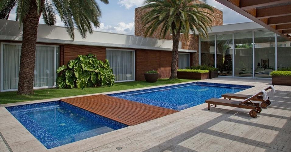 A piscina com SPA (15 m x 7 m), idealizada por Marcelo Bellotto, se alinha à arquitetura de Carla Barranco e aproveita o vão entre o corpo da casa e o espaço gourmet. Estruturado em concreto, o tanque revestido por pastilhas cerâmicas é dividido em dois por uma espécie de ponte, coberta com deck de madeira. O piso e a borda são de mármore travertino bruto e o paisagismo é tropical, com exemplares de filodendro e palmeiras