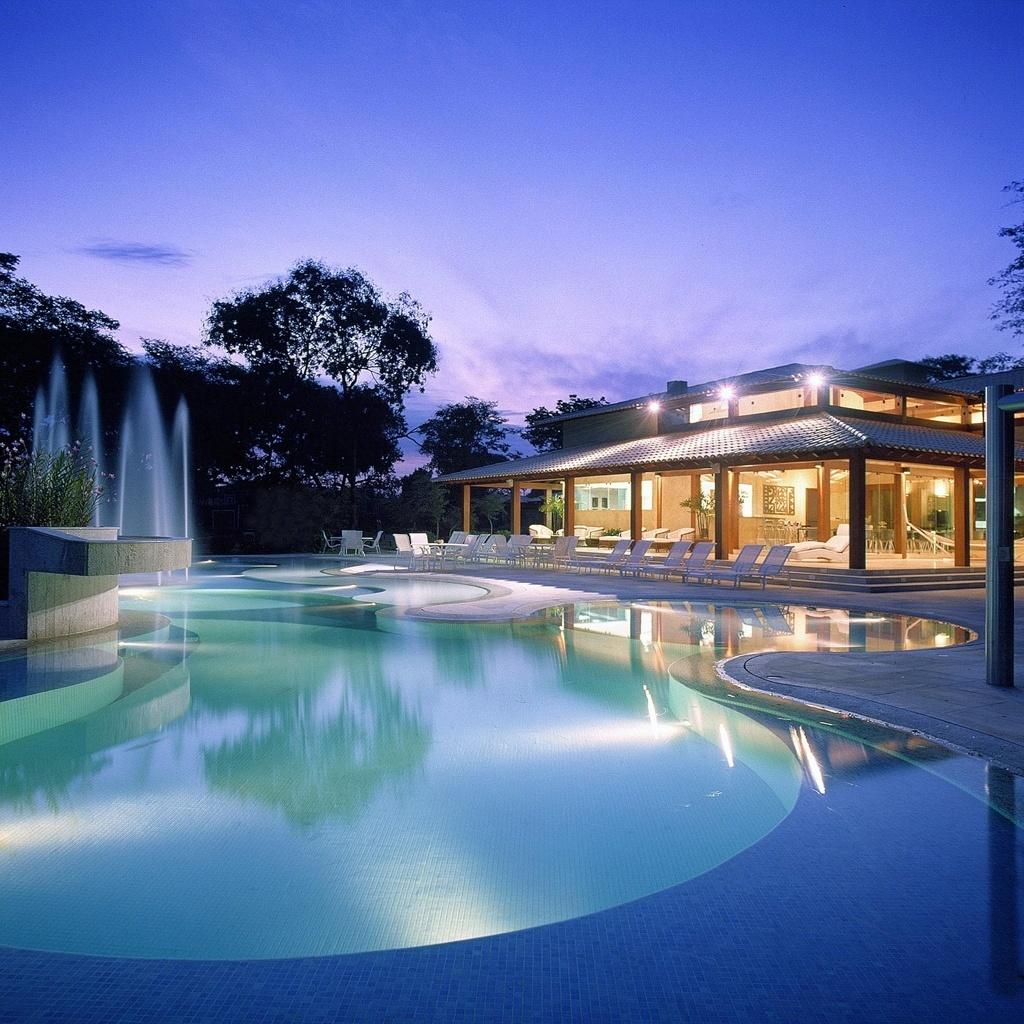 A mega piscina desta casa de fim de semana tem área de 260 m² e porção infantil (que também pode ser usada como spa) com 19,65 m², nos moldes dos resorts de Cancun, como desejava o proprietário. O projeto, assinado pela arquiteta Cristina Menezes, usa a piscina também de forma decorativa,