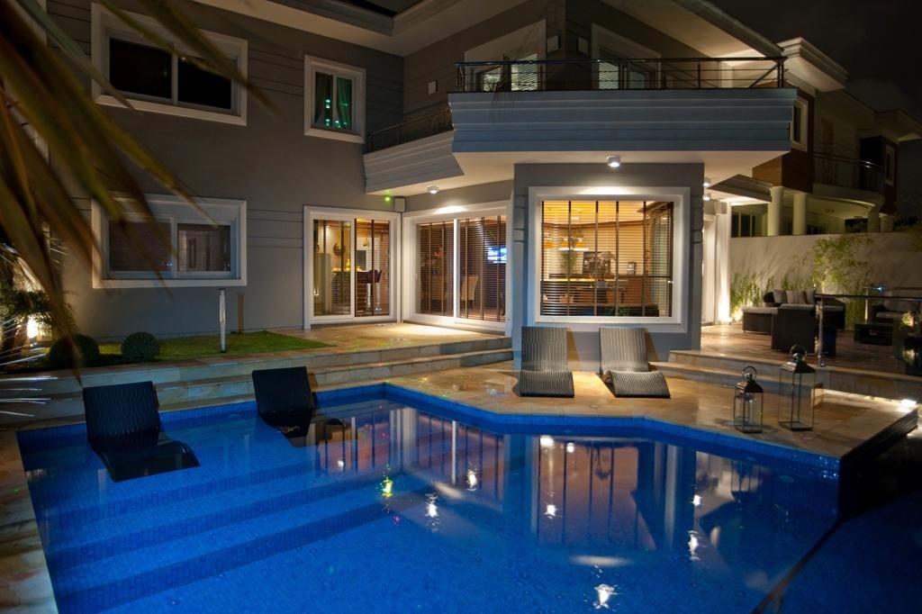 Localizada em uma casa urbana, esta piscina projetada em concreto por Paulinho Peres é revestida por pastilhas e tem bordas e piso de pedra. A iluminação LED é controlada por automação e, por ter borda infinita, o arquiteto recomenda