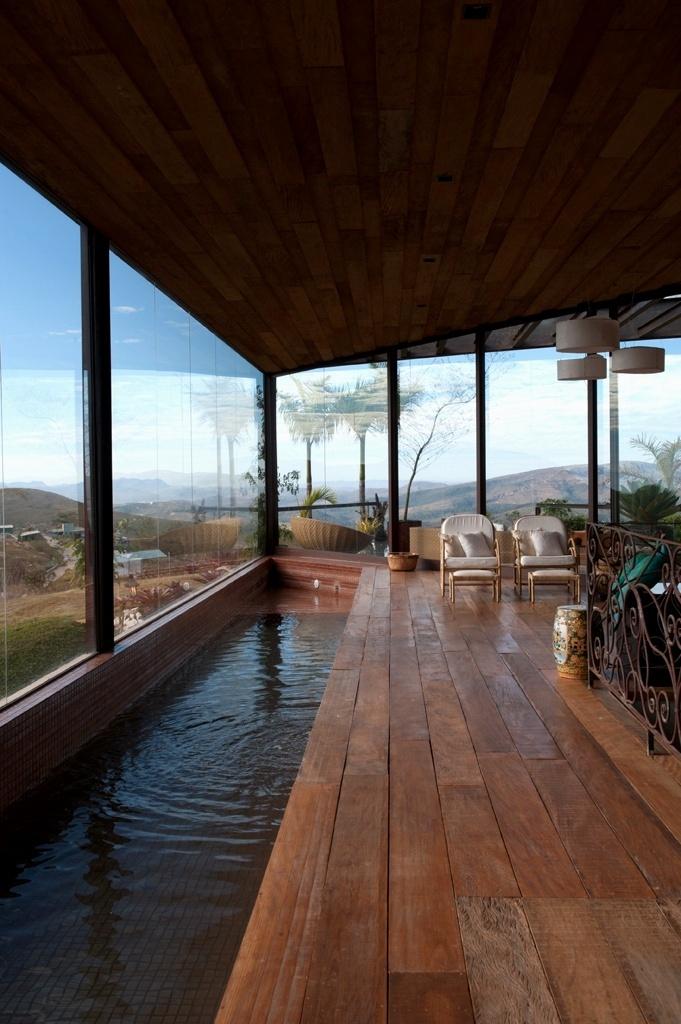 Situada no spa privativo de uma casa de montanha, esta piscina da Spati Arquitetura e Design é um exemplo de que não é necessário grandes áreas para se ter um belo tanque. O mínimo recomendado é 60 m², contando com a borda e a circulação. No formato de raia, com 14 m x 1,2 m, ela é ideal para natação. Estruturada em concreto armado, localiza-se em um espaço fechado por vidros, devido aos ventos e à baixa temperatura comuns na região. Para o acabamento, as pastilhas cobre combinam com o deck
