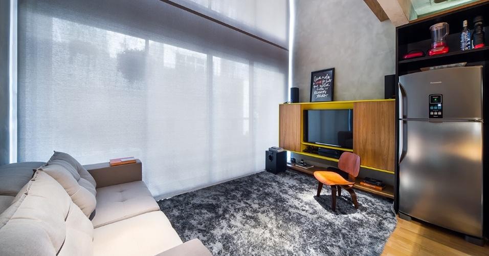 O pé-direito de 5,8 m favoreceu a entrada de ventilação e luz naturais na área do estar e do home theater. A cortina tipo painel solar, da Uniflex, controla a insolação e protege o móvel multifunção que embute a TV e pode ser usado como aparador, além de estante e armário para objetos. O elemento é da HDS Marcenaria e recebeu acabamento em laca com portas em freijó. O Apê Cobre Blue tem projeto de reforma do escritório Casa 100 Arquitetura