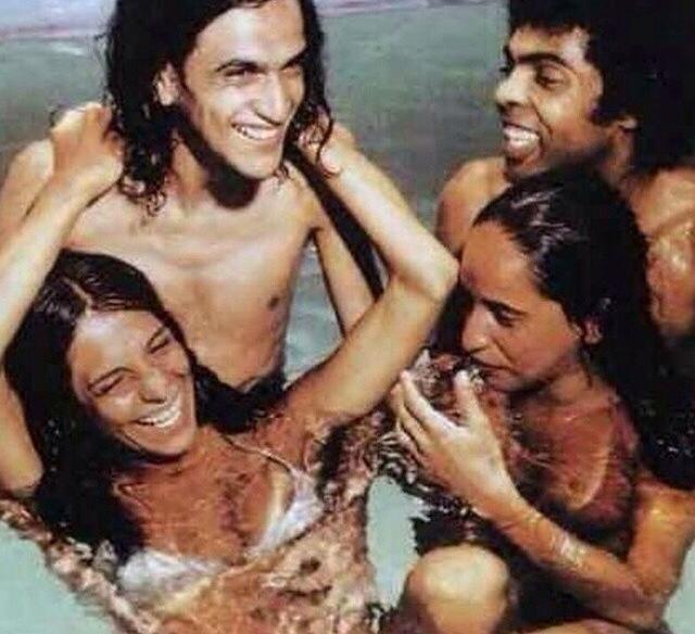 Aos risos, integrantes do grupo Doces Bárbaros se refrescam na piscina.