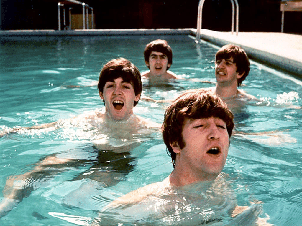 Integrantes do grupo The Beatles se divertem na piscina.