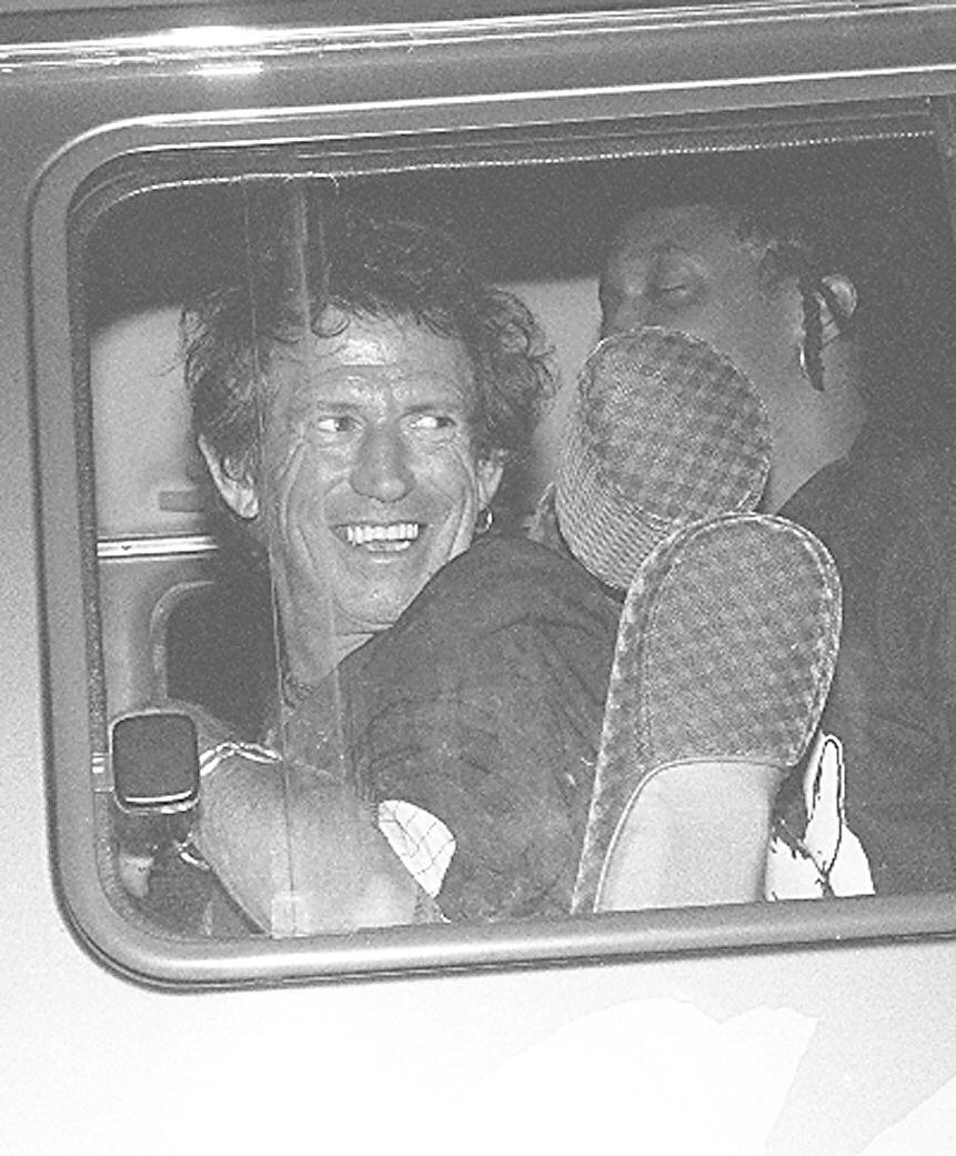 27.jan.1995 - O guitarrista dos Rolling Stones, Keith Richards, na van que o transportou do aeroporto ao hotel, atrás dele, Bernard Powler, backing vocal