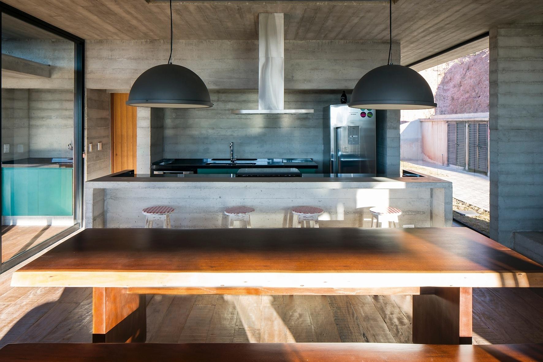 mesa de jantar é acompanhada por bancos e está posta entre a cozinha  #A15E2A 1772 1181