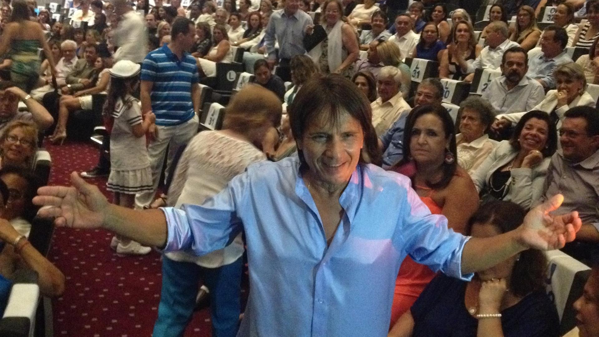 04.fev.2015 - Robson Carvalho, sósia do cantor Roberto Carlos, posa com fãs durante show no cruzeiro