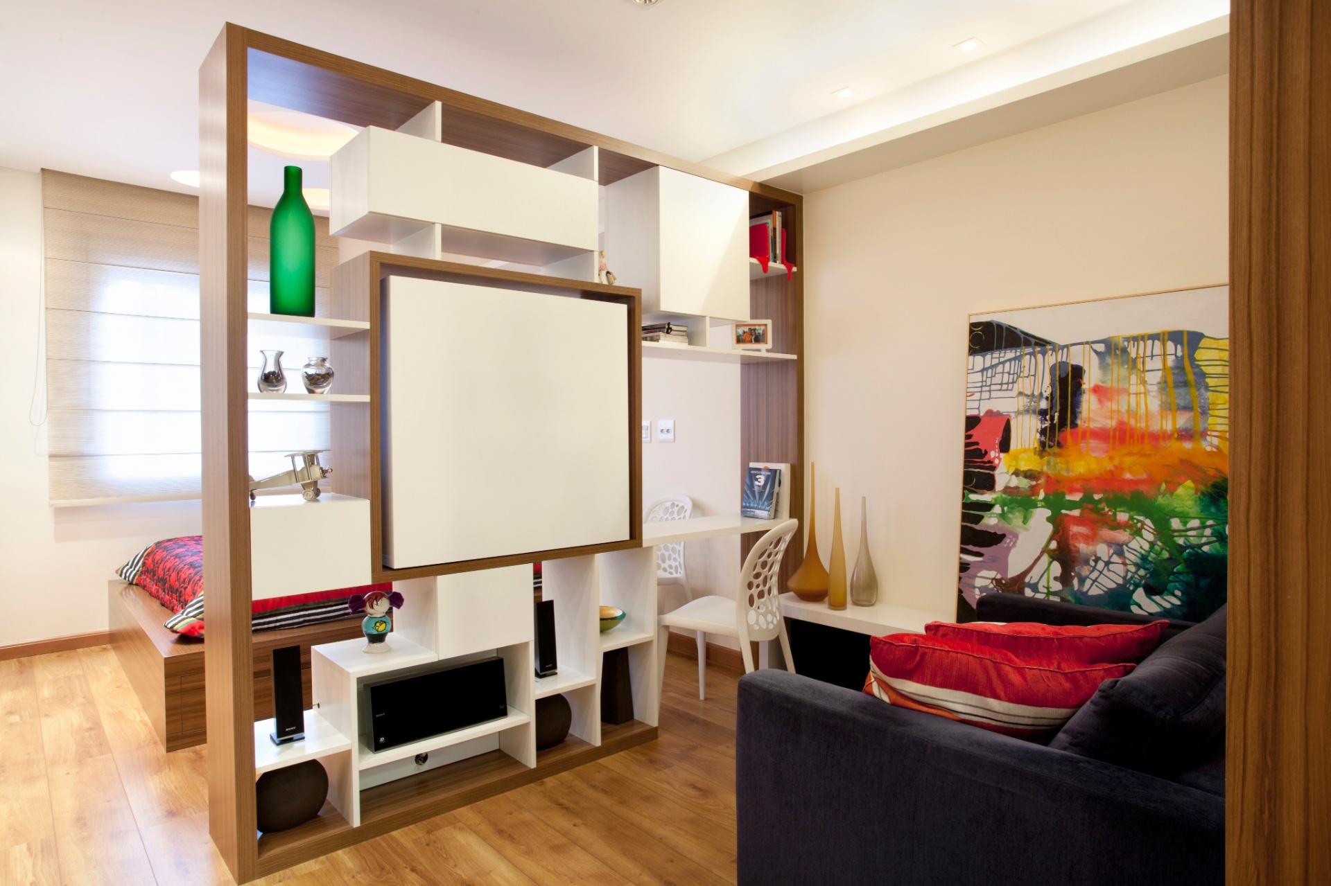 Por ter compartimento pivotante (rotatório) para TV, o eletrodoméstico pode ser utilizado tanto na sala, quanto no quarto. A prateleira suspensa (à dir. bem acima), em MDF laqueado branco, para disposição de livros se estende desde o dormitório (atrás da estante divisória). O sofá, na verdade, é uma namoradeira de veludo azul (Artefato), de tamanho menor e encaixe ideal no espaço reduzido. O projeto de interiores é de Adriana Fontana