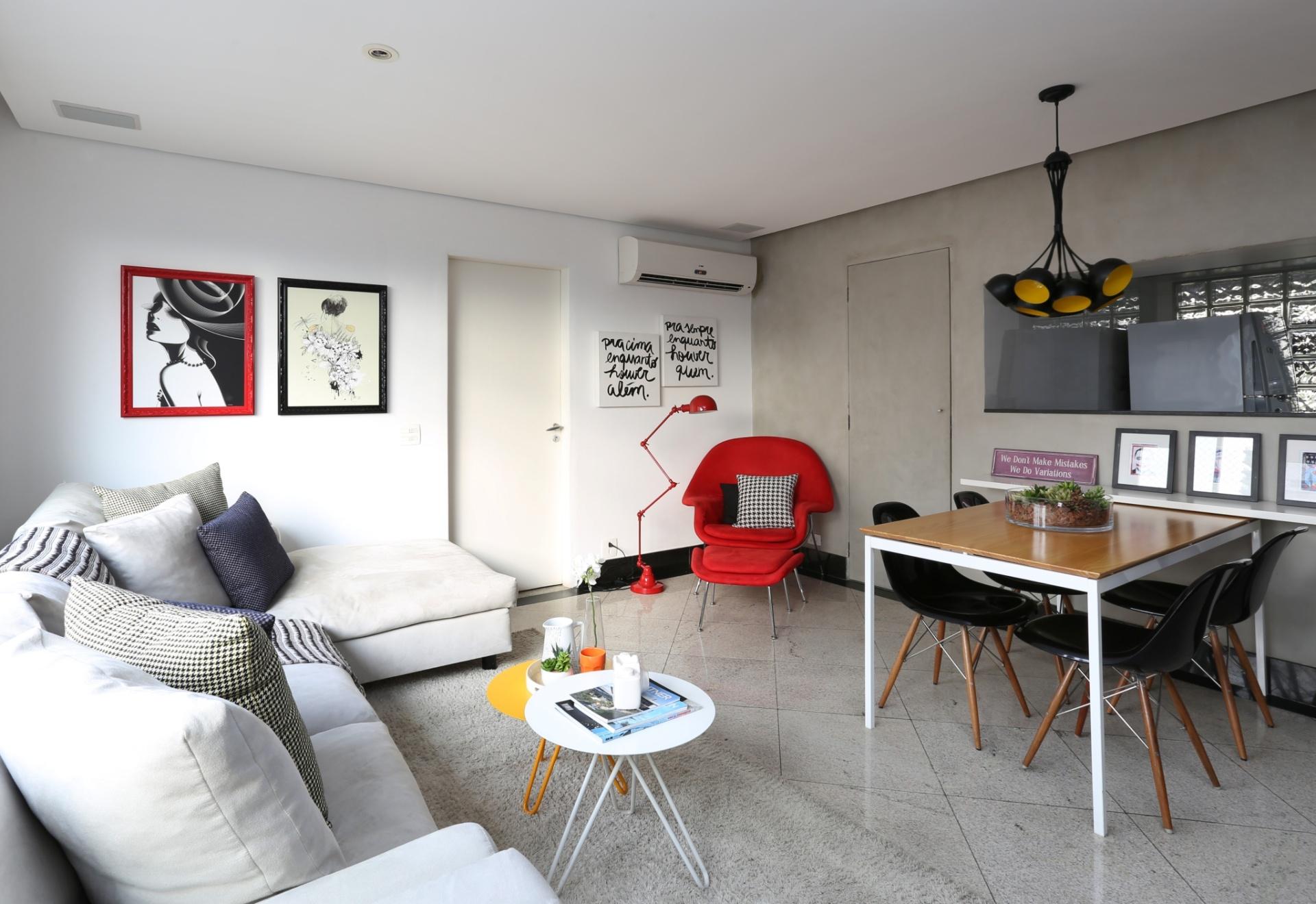 No living do apartamento em São Paulo (SP), o revestimento no padrão cimentício (Bricolagem Brasil) cobre a parede que divide o ambiente social do lavabo (mais ao fundo) e da cozinha americana. A porta do lavatório recebeu o mesmo acabamento, unificando-a com o restante da superfície. Na composição bem resolvida, as cadeiras de jantar Charles Eames Wood dialogam com a luminária pendente e com a poltrona vermelha Womb, Eero Saarinen. O projeto de reforma é assinado por Duda Senna