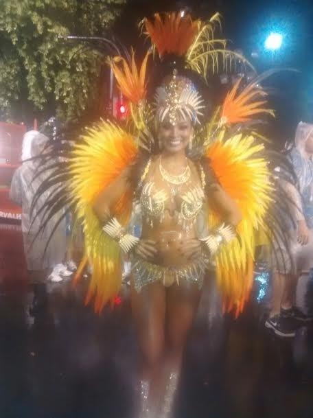 15.fev.2015 - Carol Nakamura pronta para entrar no desfile, debaixo de chuva. A ex-bailarina do Faustão está com a maquiagem manchada por causa da água, mas está animadíssima para cruzar a Sapucaí.
