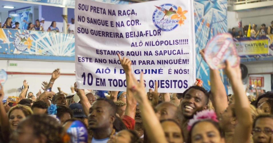 18.fev.2015 - Membros da comunidade da Beija-Flor comemoram título com faixa que faz menção à Guiné Equatorial