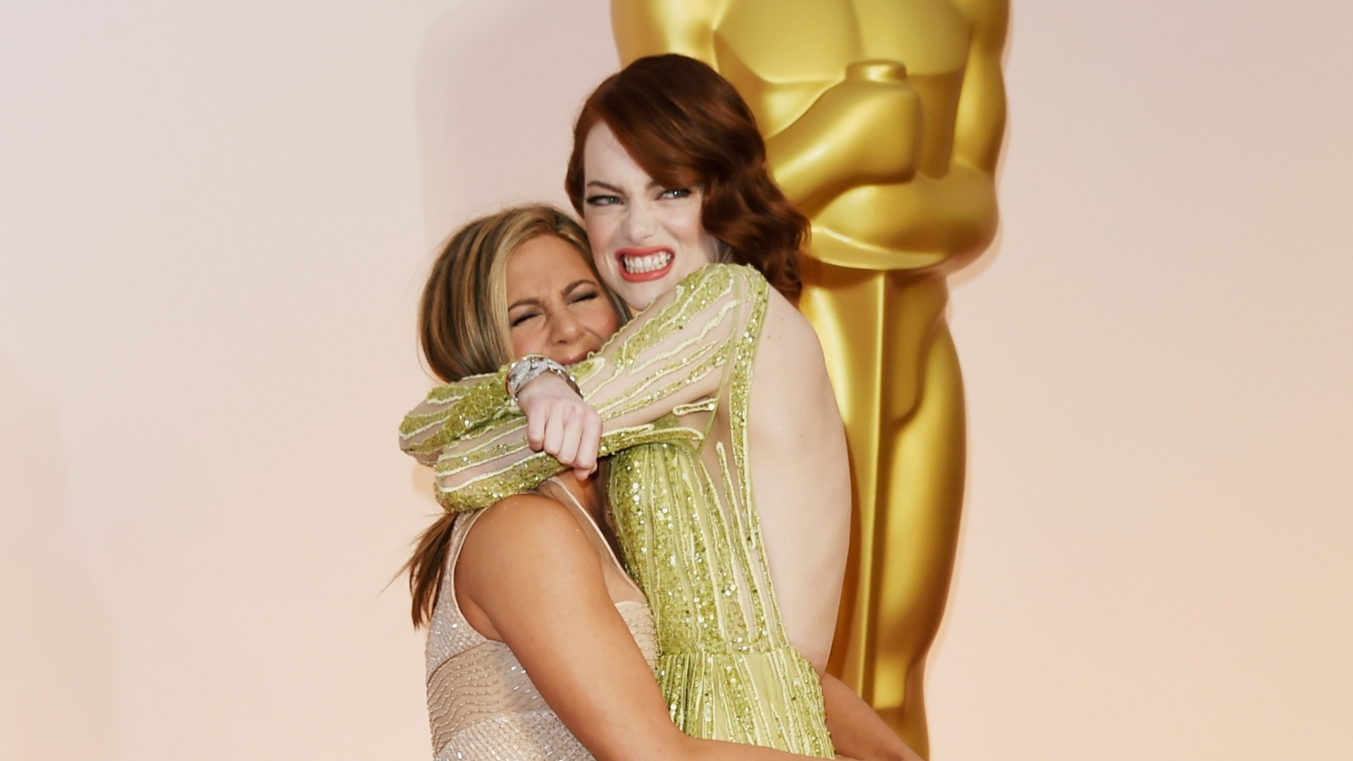 22.fev.2015 - Jennifer Aniston e Emma Stone se abraçam na chegada do Oscar 2015