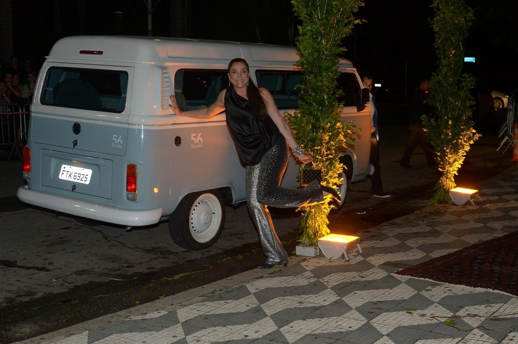 24.fev.2015 - Vestindo pantalonas, a atriz Marisa Orth posa para foto ao lado de uma Kombi na chegada para o casamento de Thiaguinho e Fernanda Souza