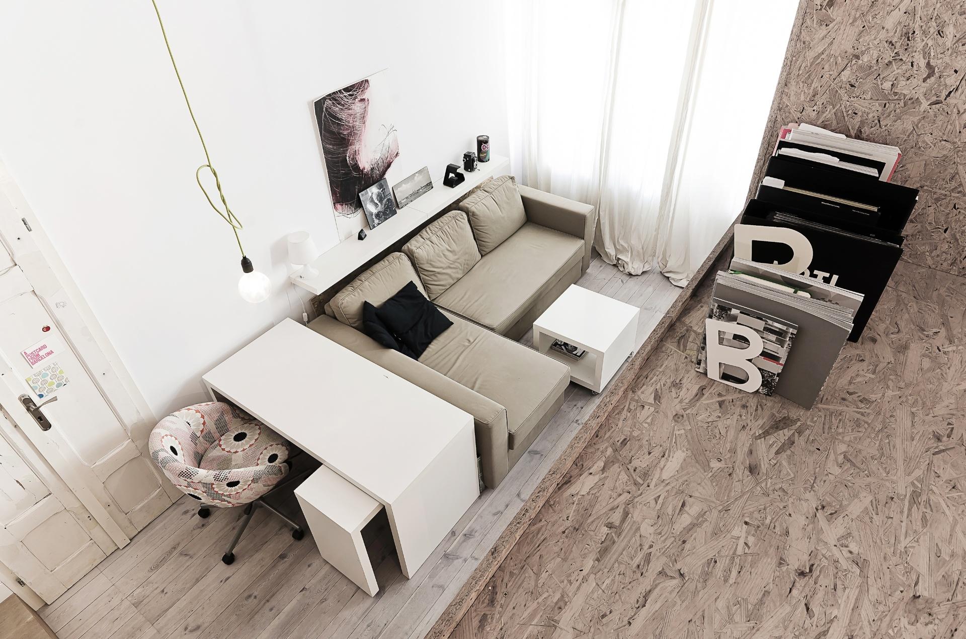 Os arquitetos do escritório polonês 3XA estudaram com precisão o tamanho e o encaixe dos móveis para a área integrada - com estar, jantar e cozinha - no apê com 29 m². A marcenaria (mesa de trabalho, prateleira de apoio ao sofá e cubo (mesa de centro)) é de MDF laqueado branco, assim como os armários embutidos de cozinha. A porta antiga que aparece na sala de estar (à esq.) é