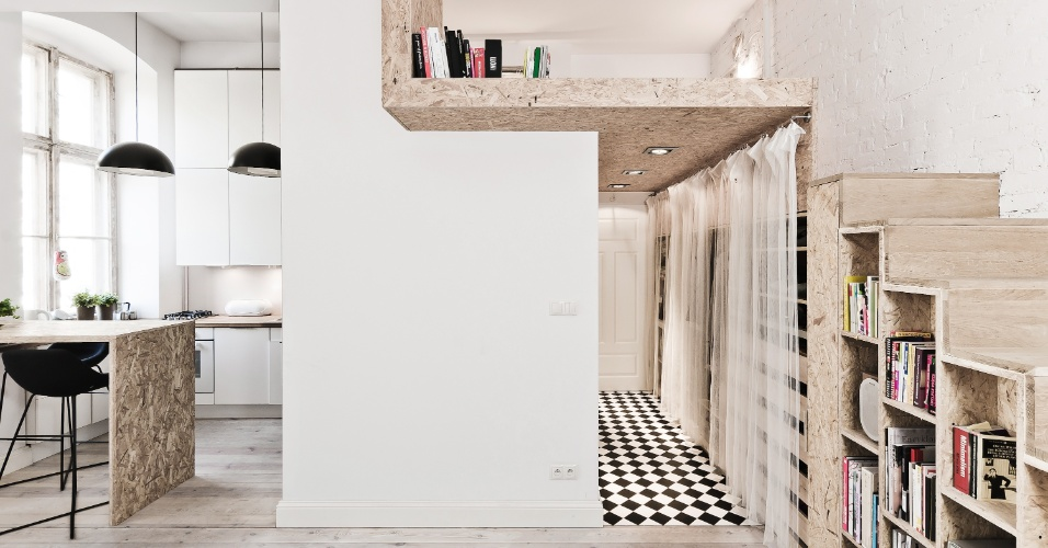 O mezanino usado como dormitório apoia-se sobre o banheiro e os guarda-roupas do apê com 29 m² na Polônia - ambos em um corredor de acesso, com piso de ladrilhos preto e branco original do edifício centenário. No corredor, o pé-direito é de 1,85 m. Elevar a cama possibilitou a integração das áreas de uso diurno e convívio social. Sob a escada, o painel de OBS (tiras de madeira prensadas e orientadas) cria uma estante. O material é leve, barato e de tons claros e o projeto é do escritório 3XA