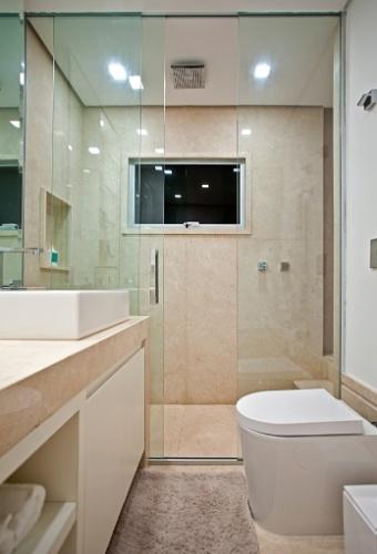 A área do banheiro, assinado pela arquiteta e designer Maithiá Guedes, é toda revestida por mármore e tem bancada generosa com armário acoplado