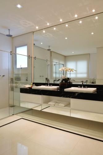 Com 25 m², este banheiro planejado pela arquiteta Leonice Alves foi revestido por mármore italiano da Parnaíba Mármores. No piso, branco Ariston, e nos filetes e na bancada, preto Nero Marquina. O espelho até o teto amplia o ambiente e se alinha aos acabamentos do gabinete. Os metais da Deca são linha Quadratta e foram customizados com Cristais Swarovski, da Decor Banho